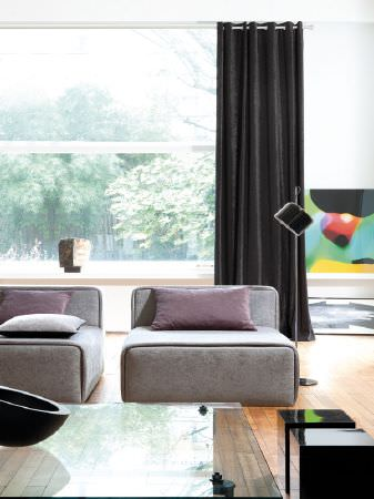 Fibre Naturelle -  Santa Cruz Fabric Collection - Low backed grey sofas with purple cushions, a glass table with a black bowl, small square black stools, black floor lamp and black curtains
