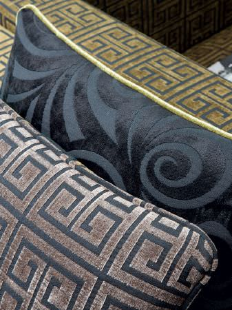 Fibre Naturelle -  Sienna Fabric Collection - Gold and black geometric sofa armrest, with a matching pewter and black geometric cushion, and a black textured cushion with a swirl design