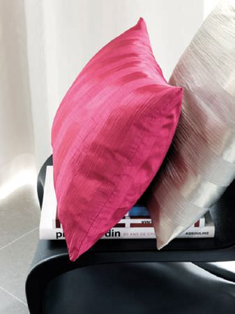 Fibre Naturelle -  Soho Fabric Collection - A hot pink cushion with a silver cushion, both with subtle stripes, on a stack of books on a black plastic moulded chair