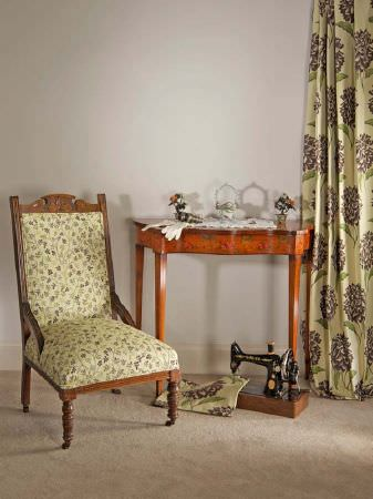 Fibre Naturelle -  Tivoli Fabric Collection - Green curtains with grey hydrangea print, a low wooden chair with green floral upholstery, a light wood table and a vintage sewing machine