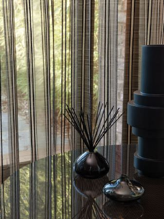 Fibre Naturelle -  Tranquility Fabric Collection - Polished round black table with black and chrome vases, reed diffusers and translucent curtains