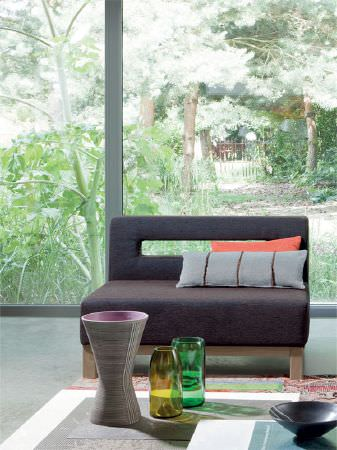 Fibre Naturelle -  Verona Fabric Collection - Dark grey sofa with cut-out in backrest, rectangular cushions in grey and orange, square white tables, ceramic/glass vases, and a black bowl