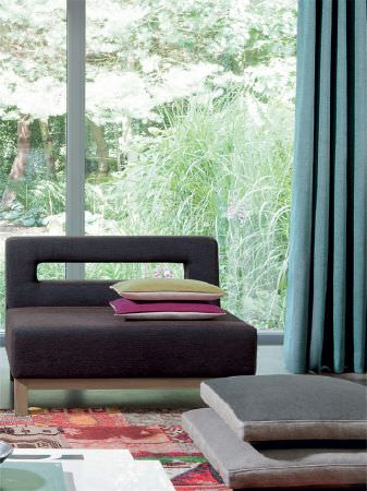 Fibre Naturelle -  Verona Fabric Collection - Cut-out style sofa with cream, magenta and green cushions, on a multicoloured rug, with large, square grey cushions and light blue curtains