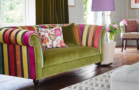 GP and J Baker -  Cosmopolitan I Fabric Collection - Velvet upholstered sofa decorated with a pattern of colourful stripes and plain seating in olive green