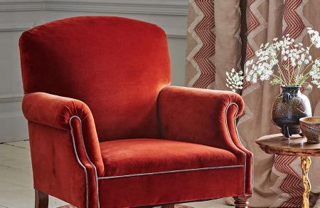 GP and J Baker -  Cosmopolitan I Fabric Collection - Vibrant red upholstered armchair and matching curtains dyed in light beige shade with red zigzag pattern