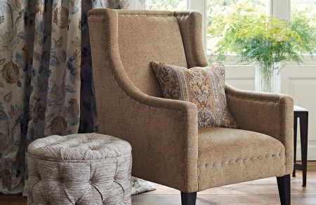 GP and J Baker -  Cosmopolitan I Fabric Collection - Plain upholstered armchair in light brown, plain light grey round ottoman and white curtains with an elegant design