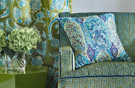 GP and J Baker -  Cosmopolitan I Fabric Collection - Green curtain decorated with bright blue floral pattern and blue upholstered sofa decorated with velvet green design