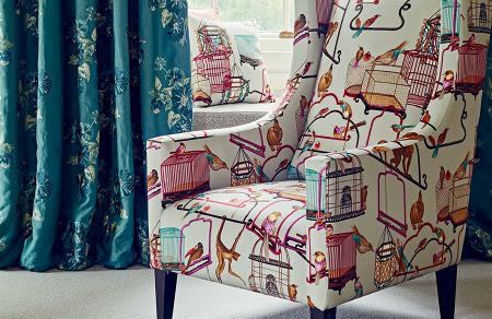GP and J Baker -  Cosmopolitan I Fabric Collection - White upholstered armchair and white cushion featuring the same colourful pattern of birds and their cages