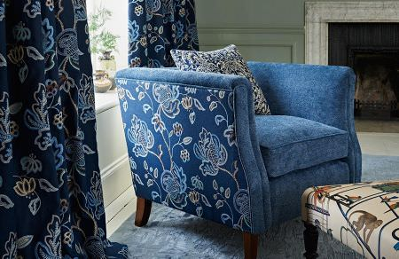 GP and J Baker -  Cosmopolitan I Fabric Collection - Dark blue curtains decorated with elegant floral design and a matching design on the sides of a plain blue armchair