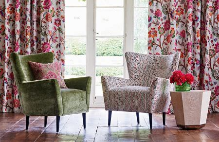 GP and J Baker -  Cosmopolitan I Fabric Collection - Vibrant floral pattern on white curtains, armchair with a plain design in green and an armchair with colourful pattern