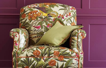 GP and J Baker -  Crayford Fabric Collection - Beige armchair decorated with a pattern of tropic flowers and yellow parrots and matching plain green cushion