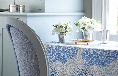 GP and J Baker -  Crayford Fabric Collection - Modern blue dining chair with a pattern of white leopard dots and a tablecloth featuring elegant leaf design