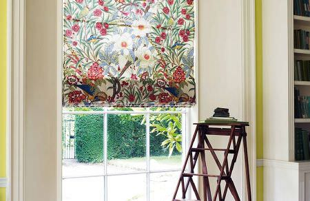 GP and J Baker -  Crayford Fabric Collection - Light beige roman blinds decorated with a pattern of tropic plants and flowers in vibrant colours