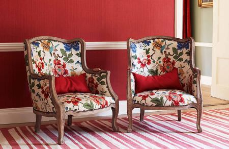GP and J Baker -  Crayford Fabric Collection - Elegant armchairs in white decorated with a vibrant pattern of tropic plants and birds and striped red carpet