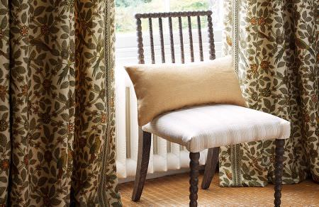 GP and J Baker -  Crayford Fabric Collection - Plain gold cushion on elegant dining chair and beige curtains decorated with dark autumn floral pattern