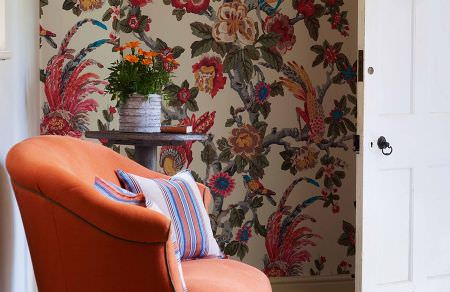 GP and J Baker -  Crayford Fabric Collection - Plain upholstered armchair in vibrant orange shade and two beige cushions decorated with colourful stripe pattern