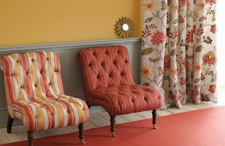 GP and J Baker -  Holcott Fabric Collection - Interesting upholstered chairs with buttons in vibrant colours and white curtain with a pattern of big flowers