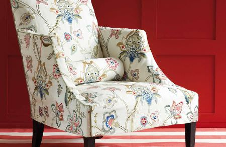 GP and J Baker -  Holcott Fabric Collection - Elegant upholstered armchair in white decorated with a colourful floral pattern and the same pattern on small cushion