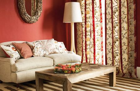 GP and J Baker -  Holcott Fabric Collection - Plain beige sofa covered with a set of colourful decorative cushions and beige curtains with elegant floral pattern