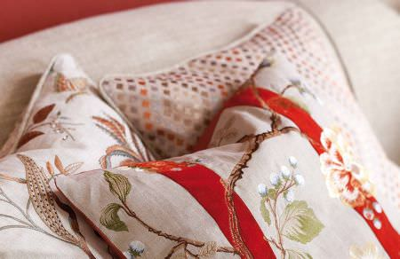 GP and J Baker -  Holcott Fabric Collection - Light grey cushion with red stripes and flowers, beige cushion with a silky diamond pattern and beige floral cushion