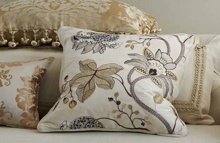 GP and J Baker -  Larkhill Fabric Collection - A close-up view of a decorative cushion in white featuring a very interesting pattern of flowers and leaves