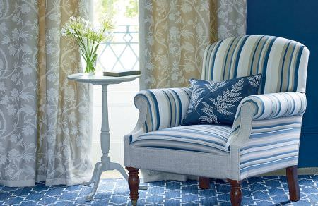 GP and J Baker -  Marwood I Fabric Collection - Beige curtain decorated with white floral pattern and a white armchair decorated with blue stripe pattern