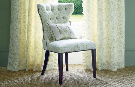 GP and J Baker -  Marwood I Fabric Collection - White curtains decorated with light beige floral pattern and white upholstered chair with the matching pattern