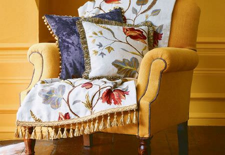 GP and J Baker -  Oleander Embroideries Fabric Collection - Vibrant armchair in orange, white floral furniture cover, plain purple cushion and white cushion with floral design