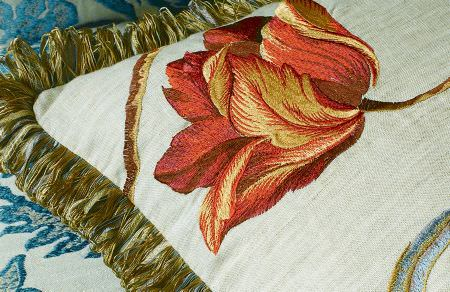 GP and J Baker -  Oleander Embroideries Fabric Collection - A close-up shot of a white cushion with gold fringes on the edges and embroidered floral pattern