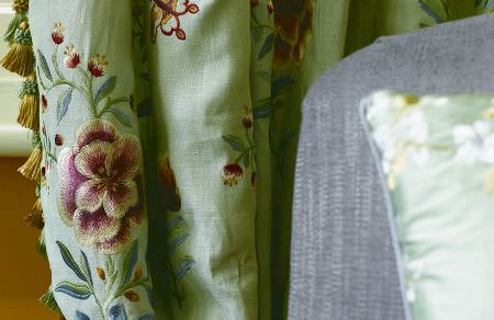 GP and J Baker -  Oleander Embroideries Fabric Collection - A close-up view of a thick curtain dyed in mint green decorated with elegant embroidered floral pattern