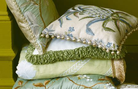 GP and J Baker -  Oleander Embroideries Fabric Collection - White cushion with blue pineapple pattern and pompoms, plain white cushion with green fringes and floral cushions