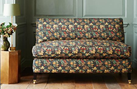 GP and J Baker -  Originals V Fabric Collection - Upholstered sofa in dark shade of grey decorated with a vibrant floral pattern in red, orange and green