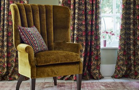 GP and J Baker -  Originals V Fabric Collection - Velvet upholstered armchair in dark yellow shade and dark curtains with vibrant floral pattern