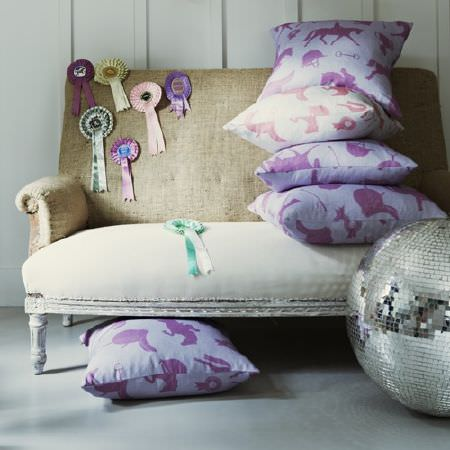 Hibou Home -  Hibou Home Fabric Collection - Purple and pale grey horse print covered cushions on a cream and light beige sofa, with rosettes and a large glitterball
