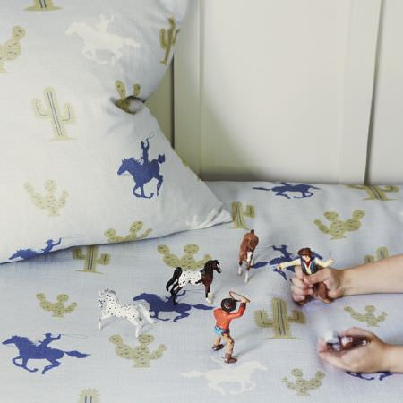 Hibou Home -  Hibou Home Fabric Collection - Toy cowboys and horses sitting on cactus and cowboy print bedding with a cushion, both made in blue, grey, khaki and white