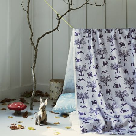 Hibou Home -  Hibou Home Fabric Collection - A branch, log, toadstool, leaves and toy hare beside a tent made from navy and white woodland themed fabric, with cushions