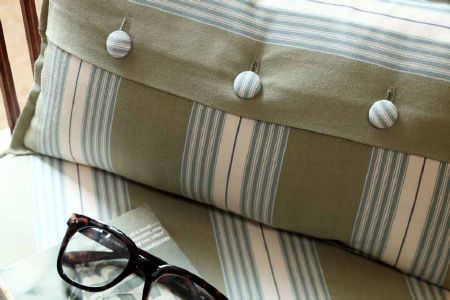 Ian Mankin -  Ian Mankin Fabric Collection - Button-down cushion with beige background and white and blue stripes, resting on fabric with similar pattern.