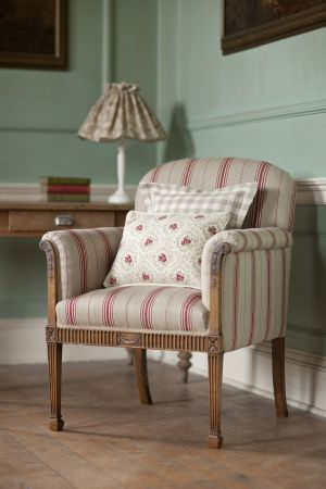 Inchyra -  Linen Ticking and Gingham Fabric Collection - Beige armchair decorated with a pattern of red stripes, light grey chequered cushion and white floral cushion