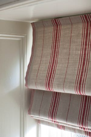 Inchyra -  Linen Ticking and Gingham Fabric Collection - Modern roman blinds dyed in light shade of grey decorated with an interesting pattern of red stripes