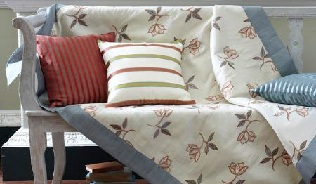 James Hare -  Ashburn Silks Fabric Collection - A distressed white wood bench with a floral patterned throw edged in blue, with three striped scatter cushions