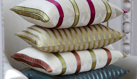 James Hare -  Ashburn Silks Fabric Collection - A white armchair with a stack of four slightly shiny striped cushions in white, green, blue, brown and fuschia