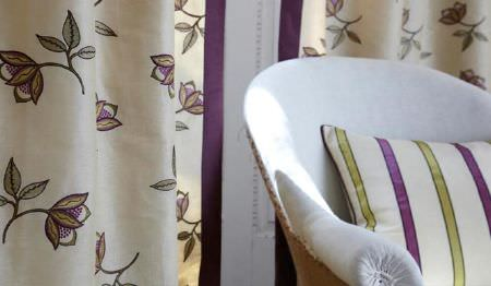 James Hare -  Ashburn Silks Fabric Collection - A white armchair with a green, purple and white striped cushion, and floral curtains with a cream, green and purple design
