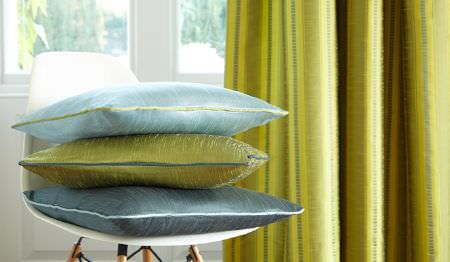 James Hare -  Astor Fabric Collection - Plain lime green curtains with a white chair and three cushions in plain lime green,sky blue and dark teal colours