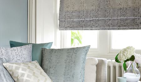 James Hare -  Aurora Silks Fabric Collection - A subtly patterned dark grey window blind with scatter cushions featuring various subtle patterns in blue and cream shades