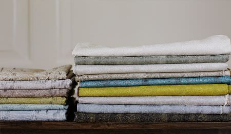 James Hare -  Aurora Silks Fabric Collection - Very subtly streaked black, mauve, lime green, denim blue, beige, grey and white fabrics folded and stacked into piles