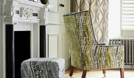 James Hare -  Carnaby Velvet Fabric Collection - Square ottoman featuring abstract design in grey and a matching yellow design on upholstered armchair