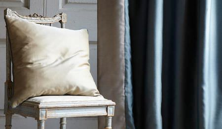 James Hare -  Connaught Silk Fabric Collection - Slightly shiny powder blue coloured curtains with a grey reverse, beside a distressed white chair and an off-white cushion
