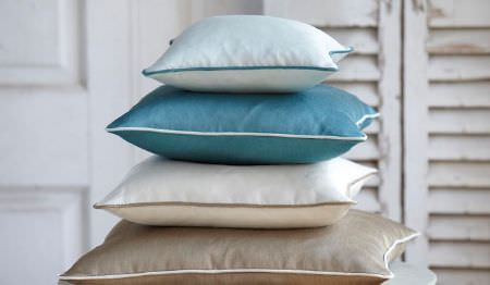 James Hare -  Connaught Silk Fabric Collection - A stack of four plain cushions, made inice blue, aquamarine,white and light grey-beige, with piping around the edges