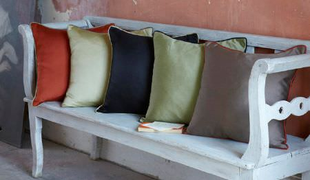 James Hare -  Connaught Silk Fabric Collection - A white bench loaded with plainterracotta, cream, navy-black,apple green and light brown square scatter cushions
