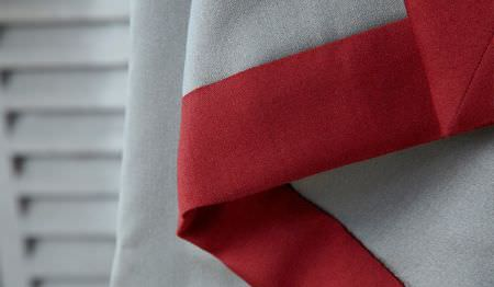 James Hare -  Connaught Silk Fabric Collection - A white shutter style door behind plain light grey fabric sewn with plain bright red coloured fabric around the edge